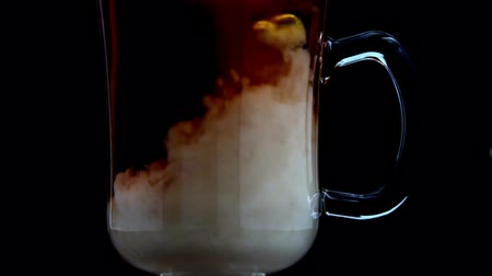 black coffee : Milk pouring into tea in a glass in slow motion