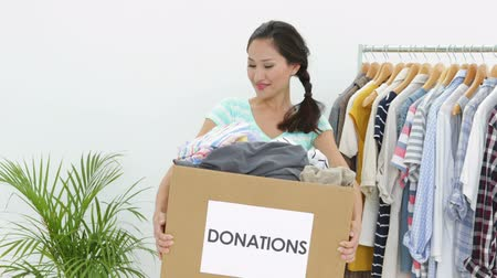 пожертвование : Pretty asian brunette holding donation box full of clothes smiling at camera