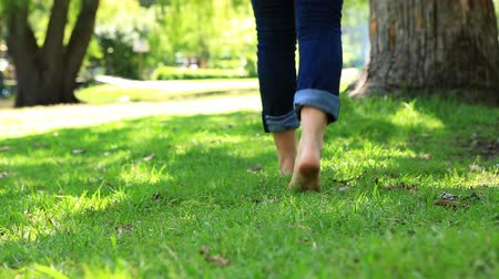 peaceful : Woman walking barefoot on the grass on a sunny day