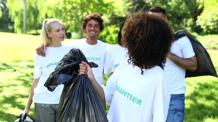 благотворительность : Happy volunteers picking up trash in the park on a sunny day