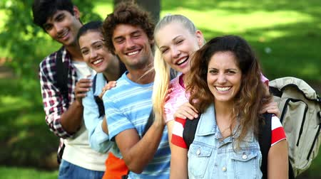 aluno : Happy students smiling at camera together on a sunny day Stock Footage