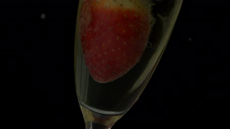 сверкающий : Strawberry falling into flute of champagne in slow motion