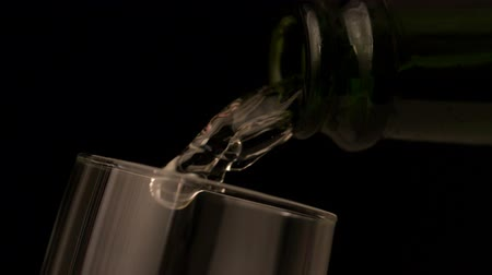 šampaňské : Champagne pouring into flute on black background in slow motion