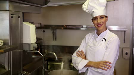chef : Pretty chef standing beside a large steaming pot in commercial kitchen