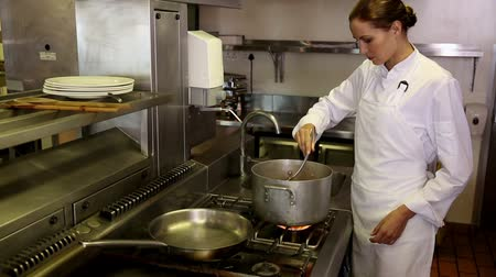 cooking pots : Pretty chef stirring a large pot in commercial kitchen
