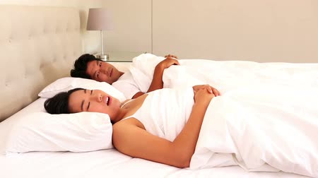 adormecido : Man covering his ears to block out snoring at home in bedroom