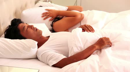 adormecido : Woman covering her ears as partner is snoring loudly at home in bedroom Vídeos