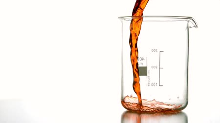 kísérlet : Orange liquid pouring into beaker in slow motion