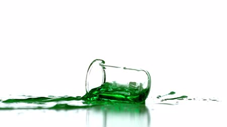 rozlití : Beaker falling and spilling green liquid in slow motion