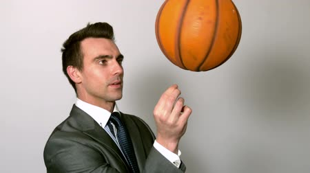 suit and tie : Businessman spinning basketball on finger in slow motion