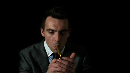 cygaro : Businessman lighting his cigar on black background in slow motion