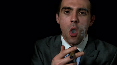 cygaro : Businessman smoking his cigar on black background in slow motion