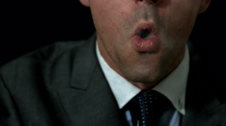 fumegante : Businessman smoking his cigar on black background in slow motion