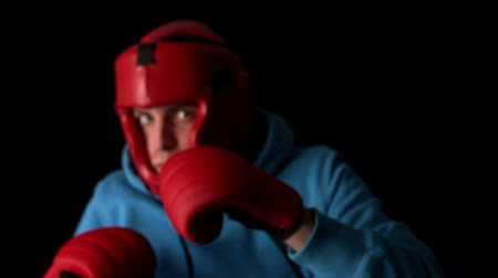 helmets : Sporty young man boxing on black background in slow motion