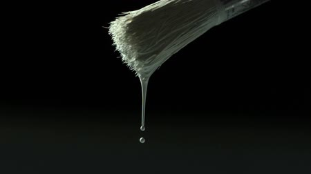 капельный : White paint dripping from paintbrush in slow motion
