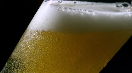 cerveja : Beer pouring into glass on black background in slow motion