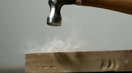 unha : Hammer hitting a nail into wooden plank in slow motion