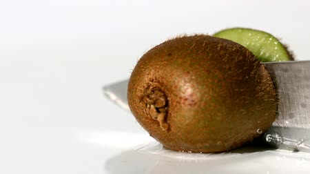 cutting up : Kiwi being sliced in half on wet white background in slow motion