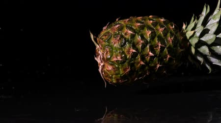 ananász : Pineapple spinning and falling on wet black surface in slow motion Stock mozgókép