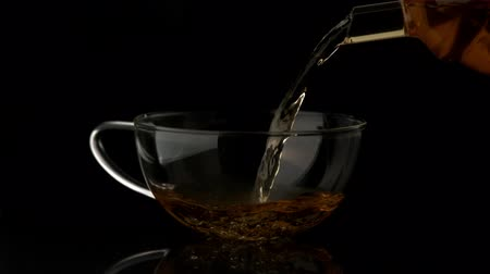 black tea : Tea pouring from teapot in glass cup in slow motion