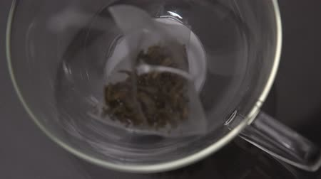 teabag : Teabag falling into glass cup in slow motion Stock Footage