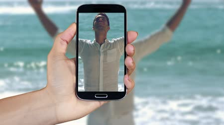 montázs : Hand showing beach and holiday clips on smartphone display montage