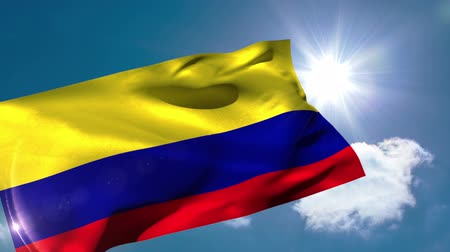 kolombiya : Colombia national flag blowing in the breeze on blue sky background with sun and clouds Stok Video