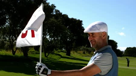 golfjátékos : Smiling golfer holding eighteenth hole flag on golf course in slow motion