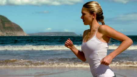 jogging : Fit blonde jogging on the beach in slow motion Stock Footage