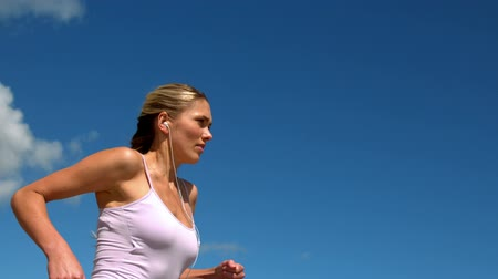 jogging : Fit blonde jogging and listening to music on sunny day in slow motion Stock Footage