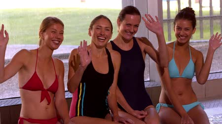 atletismo : Happy group of women sitting poolside waving at camera in slow motion Stock Footage