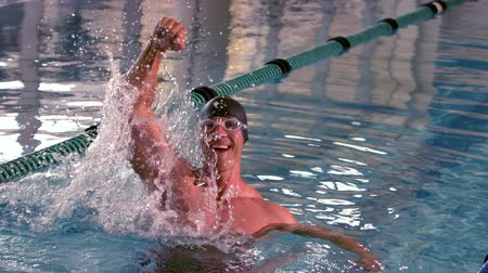 nadador : Fit happy swimmer jumping up and cheering in the pool in slow motion