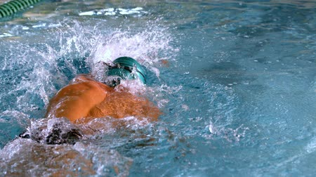 Muscular swimmer doing the front stroke in the pool in slow motion Stock Footage