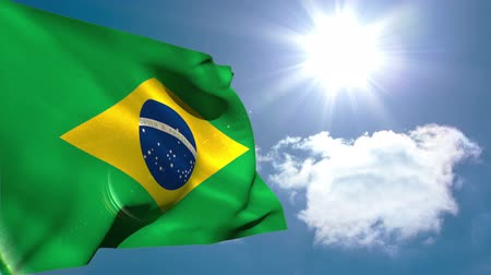 brazília : Brazil national flag waving on blue sky background with sun and clouds Stock mozgókép