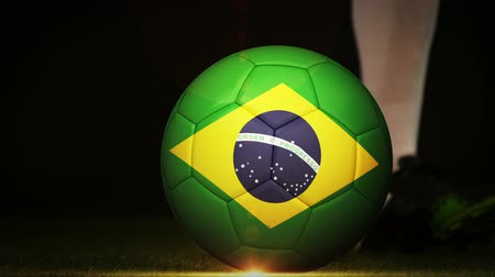 brazília : Football player kicking brazil flag ball on black background in slow motion