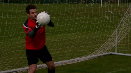 вратарь : Goalkeeper in red saving a goal during a game in slow motion