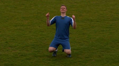 match : Football player in blue celebrating a victory in slow motion Stock Footage