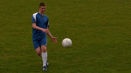 jogadores : Football player in blue kicking the ball on pitch in slow motion
