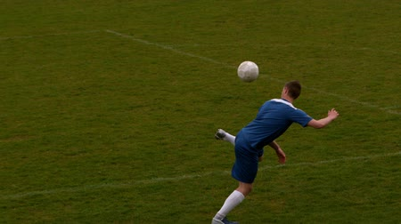 zift : Football player in blue kicking the ball on pitch in slow motion