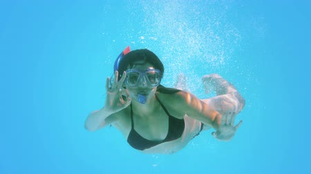 à beira da piscina : Brunette swimming underwater wearing snorkel making ok sign in slow motion Vídeos