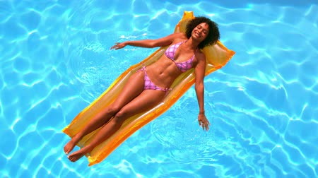 banhos de sol : Happy woman relaxing on lilo in swimming pool in slow motion