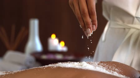 sůl : Beauty therapist pouring salt scrub on back in slow motion
