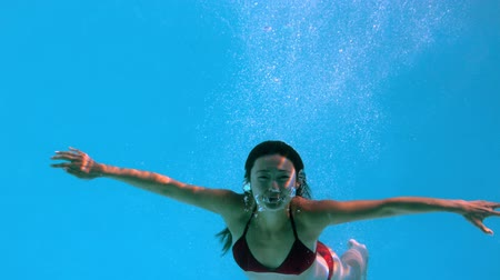 filmagens : Happy brunette underwater in swimming pool in slow motion