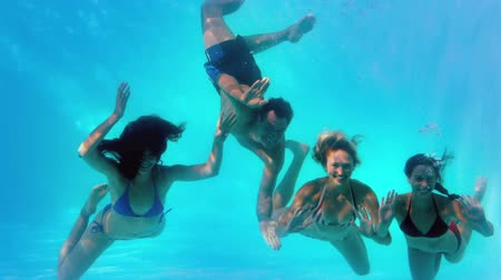 swimming underwater : Friends waving at camera underwater in swimming pool together in slow motion Stock Footage