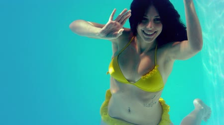 sualtı : Gorgeous brunette in yellow bikini swimming underwater in slow motion Stok Video