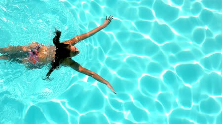 uszoda : Brunette swimming across the pool on sunny day in slow motion