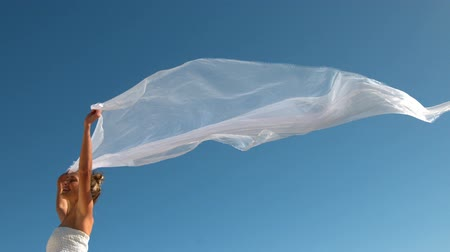 başörtüsü : Carefree blonde holding scarf up blowing in the wind in slow motion Stok Video