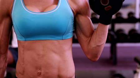 fisiculturismo : Fit woman lifting dumbbells at crossfit session at the gym Stock Footage