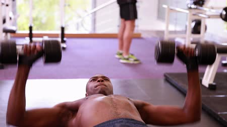 equipamentos esportivos : Fit shirtless man lifting dumbbells lying on bench at the gym Vídeos
