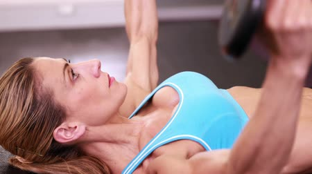 атлетика : Fit woman lying on bench lifting dumbbells at the gym